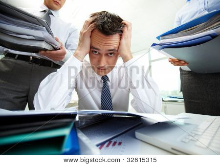 Perplexed accountant touching his head being surrounded by business partners with huge piles of documents