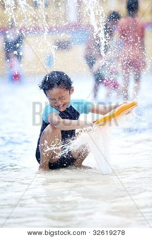 Asian Boy Playing  At Swimming Pool