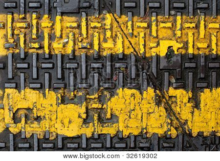 Yellow road markings on a metal drain cover.