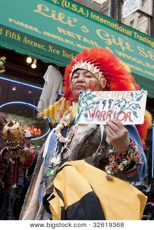 NEW YORK - MAY 1: A protester wearing a red headdress holds a sign that reads '99% Warrior ' during the march to Union Square at Occupy Wall St 'May Day' protests on May 1, 2012 in New York, NY.