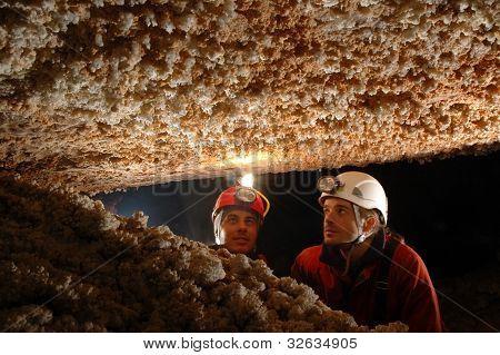 Bellas estalactitas en una cueva con dos exploradores de espeleólogo