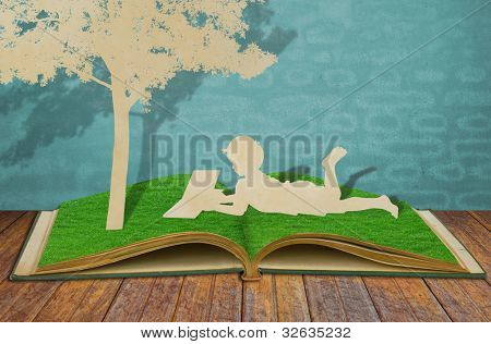 Paper cut of children read a book under tree on old grass book