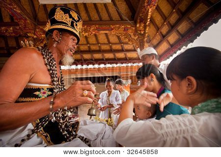 BALI, INDONESIA - MARCH 28: Unidentified child during the ceremonies of Oton - is the first ceremony for baby's on which the infant is allowed to touch the ground on March 28, 2012 on Bali, Indonesia.