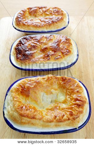 A line-up of homemade pies in traditional enamelled pie dishes