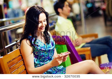 Sweet lady typing a short message on her mobile phone, her male friend can be seen in the background, shopping series