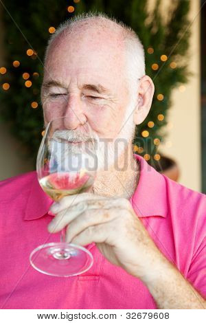 Senior man, enjoying the taste and aroma of a good glass of white wine.