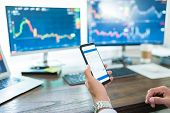 Hand Of Young Male Trader Analyzing Stock Market On Smartphone At Desk poster