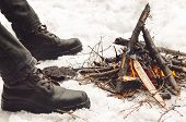 Mens Legs In Black Hiking Boots Near A Burning Bonfire. Concept Hike, Walk, Trip In Winter poster