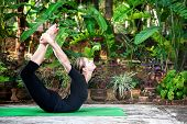 picture of dhanurasana  - Yoga Dhanurasana bow pose by woman in black cloth in the garden with palms banana trees and plants in the pots - JPG