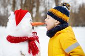 Little Boy Playing With Funny Snowman. Child Reaches For A Snowmans Carrot Nose And Wants To Bite.  poster
