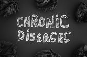 The Words Chronic Diseases On A Black Background With Black Crumpled Paper Balls Around It. Black An poster