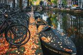 Bicycles Parked Along An Amsterdam Canal In Fall Colors In The Netherlands poster