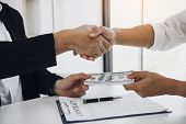 Two Corporate Businessmen Shaking Hands While One Man Places Money On Document In Office Room With C poster