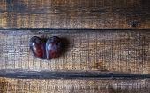 Ugly Plum. A Spoiled Purple Heart-shaped Plum On A Brown Wooden Background. Ugly Fruit. Funny Food.  poster