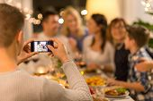 celebration, holidays and people concept - man with smartphone taking picture of family at dinner pa poster