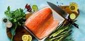 Banner Of Fresh Salmon Slice On A Wooden Cutting Board With Fresh Aromatic Herbs And Asparagus On Th poster