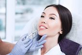 Woman Having Lip Injections, A Prick Of A Syringe For The Beauty Lips. Lip Augmentation poster