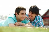image of gay couple  - Happy gay lovers lying on the lawn - JPG