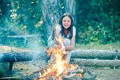 Happy Girl On A Camping Trip Relaxing By Campfire. Girl Backpackers Relaxing Near Campfire poster