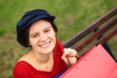 image of newsboy  - Happy young Caucasian woman with shopping bags sitting on a bench  - JPG