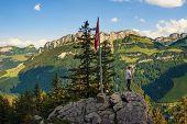Tourist Enjoys Spectacular Views Over Appenzell Alps Under Swiss Flag Standing On The Ebenalp Mounta poster