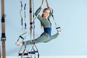 Photo Of Beautiful Young Sporty Woman. Female Trainer In Sportswear Workout With Suspension Strap At poster