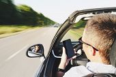 Closeup Of A Man Using A Smartphone While Driving A Car. Driving Into Oncoming Traffic. Dangerous Mo poster