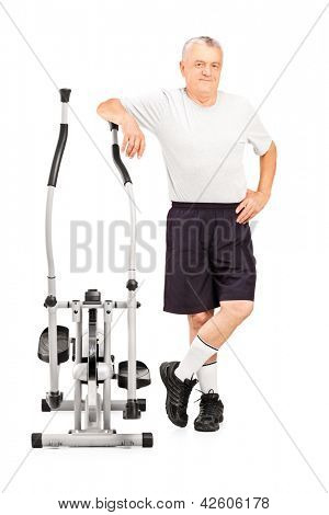 Full length portrait of a mature athlete standing next to a cross trainer machine isolated on white background