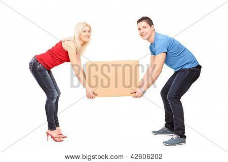 Full length portrait of a young couple trying to lift a box isolated against white background