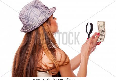 Long hair brunette with hat looking American hundred Dollar bill through magnifier glass