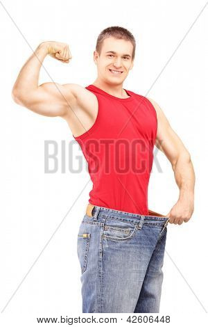 Weight loss man in an old pair of jeans showing his muscular body isolated on white background