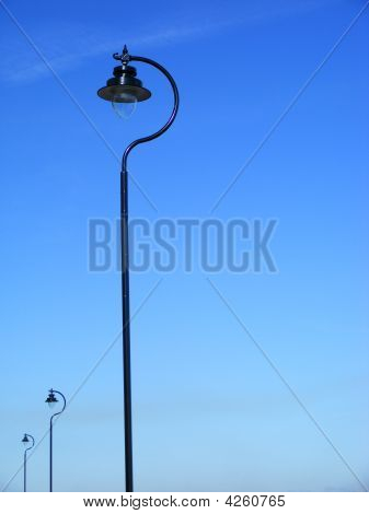 Three Black Lamposts Against Blue Sky