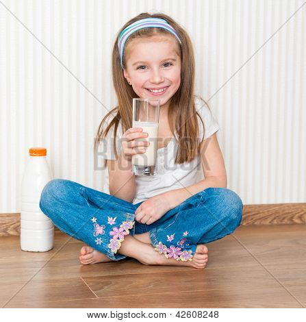 little smiley girl drink the milk  on the floor