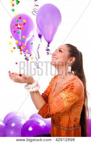 smiling girl catching falling sweets and candies