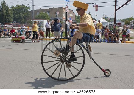 Man Riding High Wheel Bicycle Side View