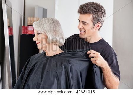 Male hairdresser removing female client's apron after haircut at salon