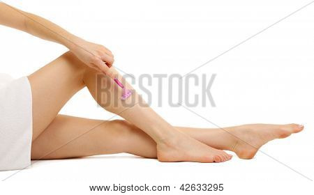 Beautiful woman is shaving her leg, isolated on white