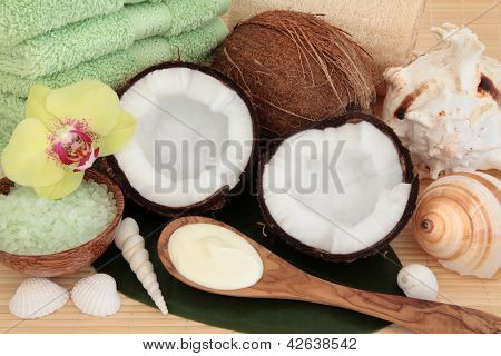 Coconut spa products with body moisturiser, green bath salts, exfoliating scrub, towels and sea shells over bamboo and leaf background.