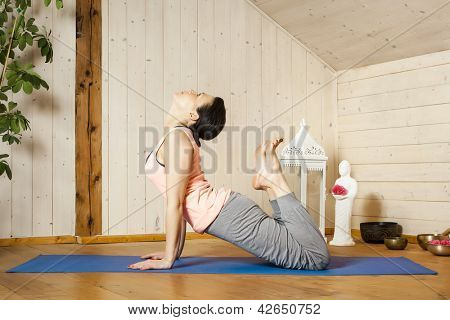 An image of a pretty woman doing yoga at home - Urdhva Mukha Shvanasana