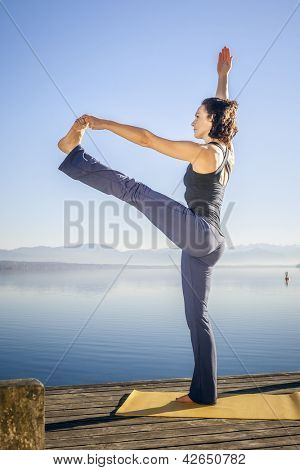 An image of a pretty woman doing yoga at the lake - Utthita Hasta Padangusthasana