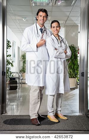 Full length portrait of multiethnic medical professionals standing together at hospital entrance