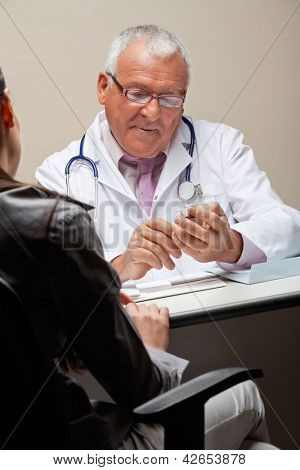 Senior male doctor going through a medicine box while female sitting on chair