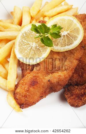 Viener schnitzel, breaded steak with french fries and lemon