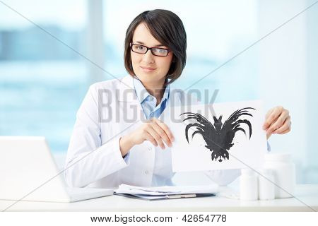 Smiling psychologist showing paper with Rorschach inkblot
