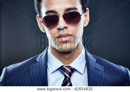 Portrait of calm man in sunglasses looking at camera