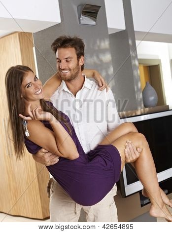 Attractive young couple enjoying new home, smiling happy. Man holding woman in his arms.