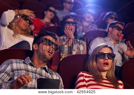 Audience watching 3D horror movie in cinema.