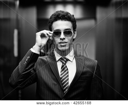 Portrait of confident man in suit and sunglasses looking at camera