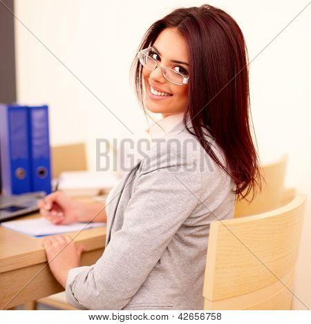 Young beautiful woman working in office. Making notes and looking back at camera.