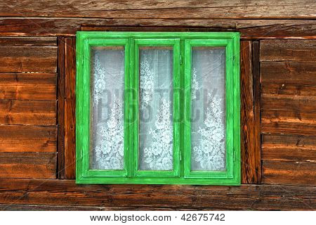Green window of a rustic old house with wooden walls